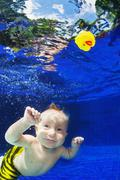 Child swimming underwater in blue pool for yellow toy Stock Photos