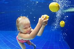 Child swimming underwater in blue pool for yellow lemon - stock photo