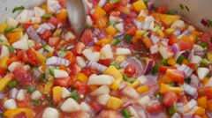 Stirring homemade peach salsa in kitchen Stock Footage