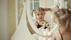 Mother combing her funny daughter in front of the mirror. Dolly shot. Stock Footage