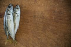 Raw fish (scad) over natural wood background Stock Photos