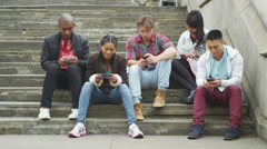 4K Attractive group of friends all looking at smartphones outdoors in city Stock Footage