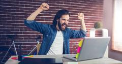 Stock Photo of Cheerful creative businessman with arms raised looking at laptop