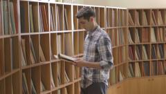 Student looking for a book in the library Stock Footage