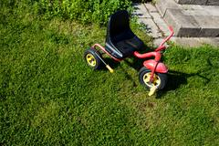 Stock Photo of Childhood. Small red tricycle cycle toy on grass.