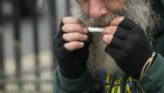 Old man smoking in the street Stock Footage