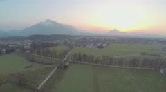 Beautiful mountains hiding sun on horizon, green farming fields, amazing sunrise Stock Footage