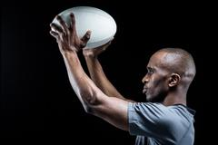 Athlete in position of throwing rugby ball - stock photo