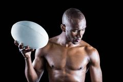 Concentrated shirtless sportsman holding rugby ball - stock photo