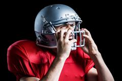 Aggressive American football player holding helmet - stock photo