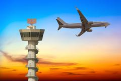 Commercial airplane flying over airport control tower at sunset Stock Photos