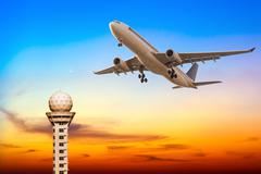 Commercial airplane take off over airport control tower at sunset - stock photo