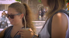 Young women couple travelers buying coffee from street vendor - stock footage