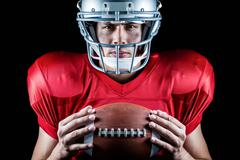 Close-up portrait of confident American football player holding ball - stock photo