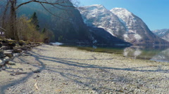 Beautiful stony lakeside in Austrian Alps, mountain lake, low season at resort Stock Footage