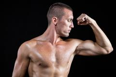 Serious shirtless athlete flexing muscles - stock photo