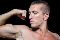Close-up serious shirtless athlete flexing muscles - stock photo