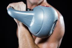 Close-up of shirtless sportsman working out with kettlebell Stock Photos