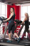 Sporty girls walk on treadmill Stock Photos