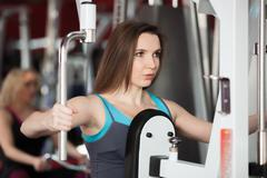 Girl exhales while doing exercises with weights on training apparatus Stock Photos