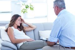 Thearapist advising pregenat woman on sofa - stock photo