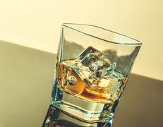 glass of whiskey on table with reflection, warm atmosphere - stock photo