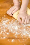 Woman's hands knead dough on the table - stock photo