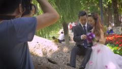 Young Asian bride and groom have wedding photos taken of them in park Stock Footage