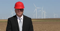 Chief Engineer Man Looking Camera Wind Turbines Farm Green Energy Windmills Spin Stock Footage