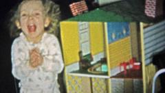 1957: Rich girl smiliing playing with oversized dollhouse. Stock Footage
