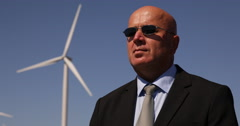 Security Guard One Man Guarding Wind Turbine Farm Power Plant Field Surveillance - stock footage