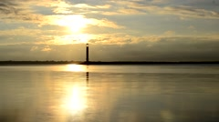 Time lapse of water landscape with lighthouse and clouds at dawn Stock Footage
