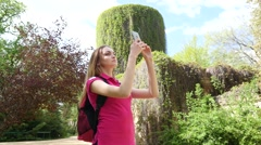 Teen girl make photo of showplace in park via smart phone camera Stock Footage