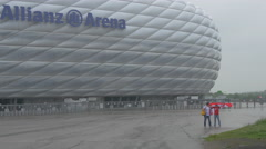 Two people standing in front of Allianz Arena in Munich Stock Footage