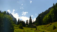 Alps montains clouds shadows small chalet swiss large shot Stock Footage