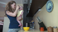 Woman hold her baby daughter and feed with spoon in kitchen. 4K Stock Footage