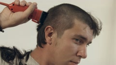 Guy shaves off hair on the head with the help of the electric shaver for Stock Footage