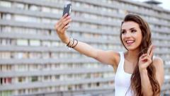 Pretty young woman taking selfie with smartphone on the rooftop Stock Footage