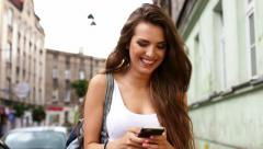 Closeup of happy young woman typing on smart phone on city street Stock Footage