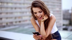 Young woman typing on smart phone sitting on the rooftop Stock Footage
