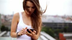 Attractive woman on the rooftop using smartphone Stock Footage