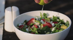 Squeezing lime on a salad Stock Footage