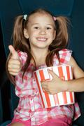 Thumbs up for impressive movie - stock photo