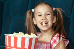 Adorable little girl with popcorn - stock photo