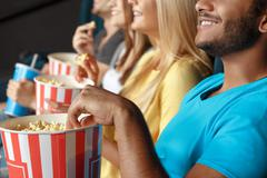 Friends eating popcorn at the movie theatre Stock Photos