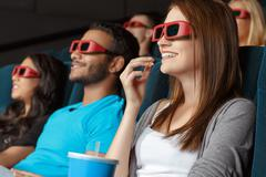 Friends watching 3D movie in the cinema Stock Photos