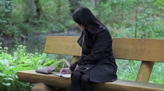 Women listening to music and writing on the bench in the park Stock Footage