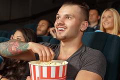 Young man laughing during a comedy film - stock photo