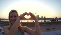 Girl making heart shape with hands with St. Louis Arch in background Stock Footage