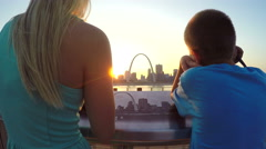Pan up of brother and sister looking at scenic St. Louis Arch Stock Footage